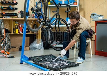 Young mechanic taking handtool from toolkit while repairing cycle wheel