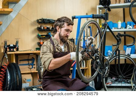 Young master in working gloves and apron repairing wheel of bicycle in workshop