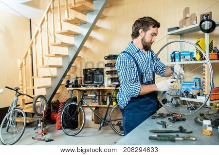 Young man in uniform and gloves repairing wheel of bicycle in workshop