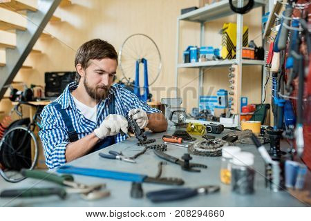Modern mechanic repairing chain from bicycle wheel by his workplace