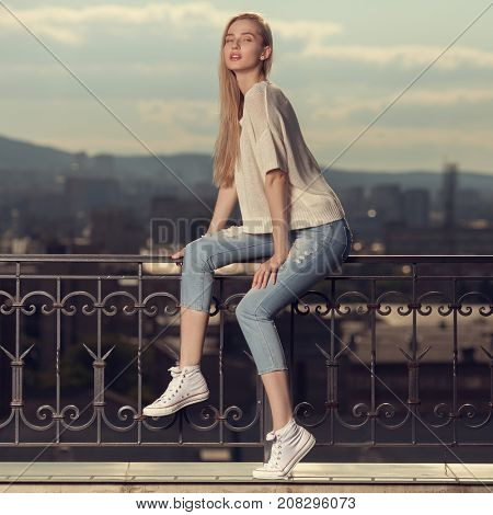 Fashion portrait of young blonde woman. Jeans and sneakers.
