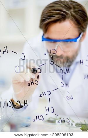 Confident middle-aged scientist writing structural chemical formula on a glass board while working at modern laboratory, he wearing safety goggles and white coat