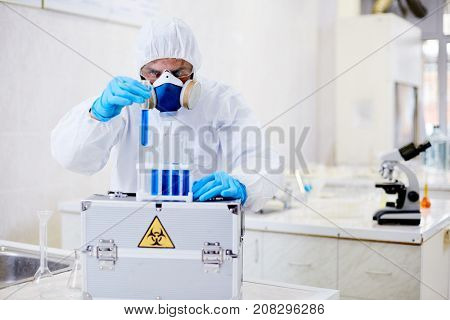 Talented virology research scientist wearing coverall and respirator working with biohazard substance while conducting experiment at modern laboratory