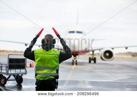 Ground Crew Signaling To Airplane On Wet Runway