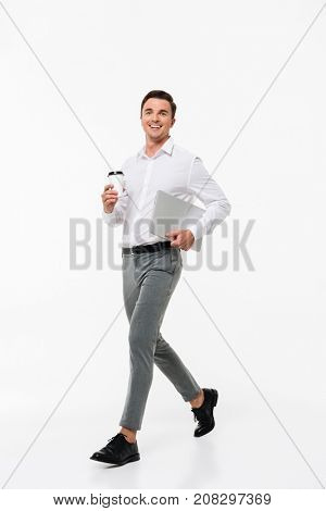 Full length portrait of an attractive joyful man in a white shirt holding laptop computer and coffee cup while walking and looking at camera isolated over white background