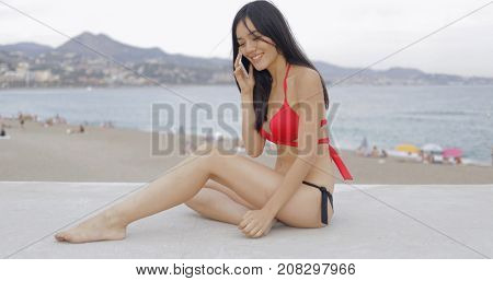 Fit young model in bright bikini posing on concrete fence talking smartphone and laughing on background of tropical beach and sea.