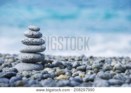 Stones pyramid on pebble beach, stability, zen, harmony, balance concept. With blur sea background on a sunny day in italy, Calabria, Tropea