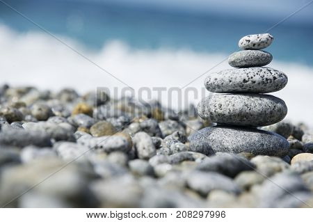 Stones pyramid on pebble beach, stability, zen, harmony, balance concept. With blur sea background on a sunny day in italy