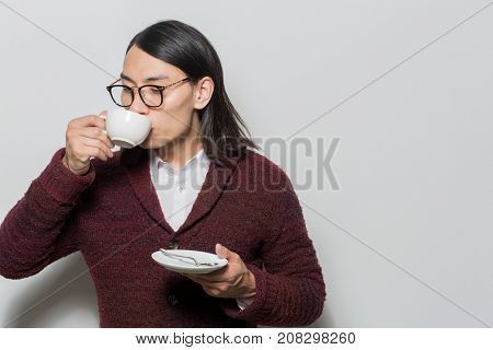 Young Asian man holding saucer with spoon while sipping hot drink from cup
