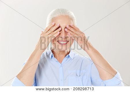 Senior grey-haired woman covering her eyes with both hands, isolated over white background