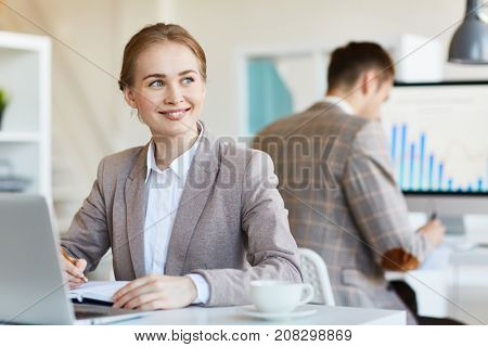 Happy young manager making notes in notebook by her workplace in working environment