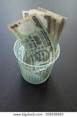 Indian currency notes in a miniature waste bin. A concept for an Indian inflation and economy.