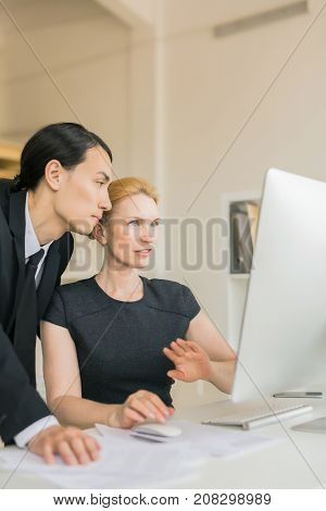 Two colleagues looking at online data in computer monitor at meeting