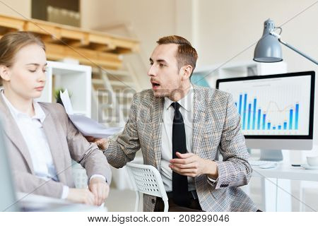 Annoyed boss with papers scolding his subordinate in office