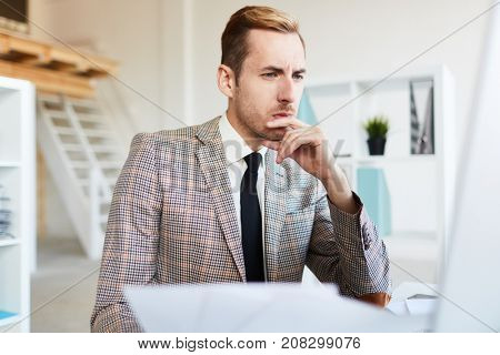 Thoughtful or skeptical businessman looking through online statistics