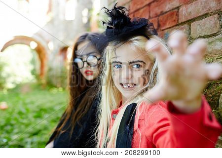 Gloomy halloween girls with frightening expression looking at camera