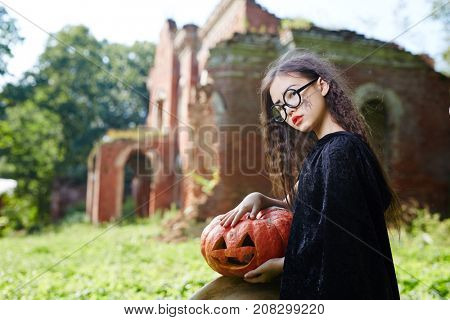 Little witch with halloween pumpkin sitting in natural environment