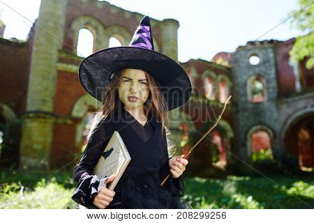 Sulky little in black attire and hat holding book and magic stick