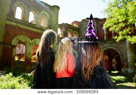 Three girls in witch attire going to play halloween tricks on people