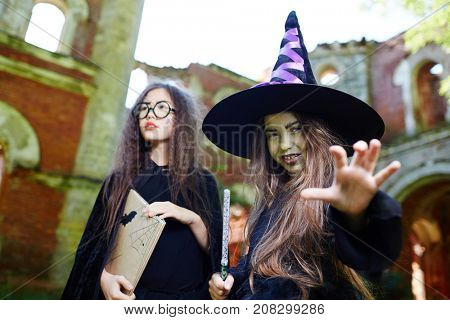 Little witch in black hat and warlock and her friend with book frightening people in abandoned place
