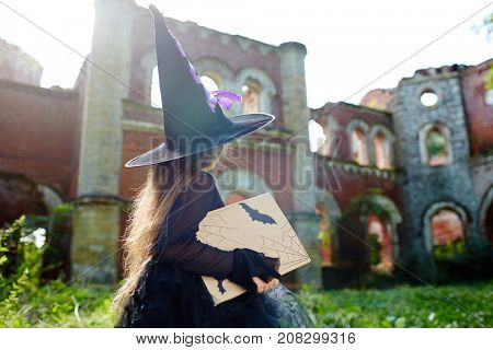 Little witch with book of spells walking towards her castle in abandoned place