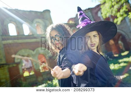 Spooky witches in halloween attire pointing at you by their magic sticks