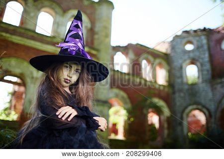 Creepy girl in large witch hat and black attire looking at camera
