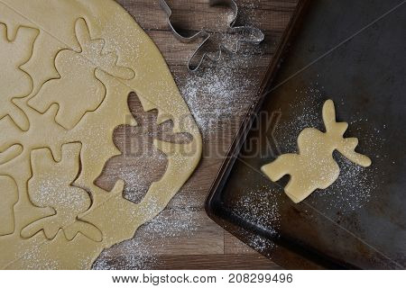 Top view of a baking sheet with a moose shaped cookie, with dough and additional moose shapes in raw dough.