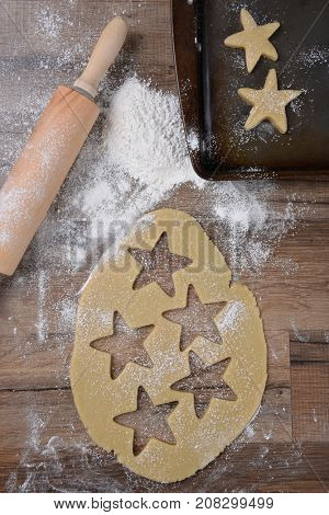 Top view of raw cookie dough with star shapes and cookie cutter on wood table with a rolling pin and flour sprinkles and baking sheet.