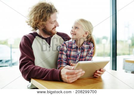 Contemporary child and her father with tablet spending leisure by watching curious video or movie and discussing it