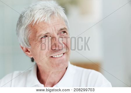 Headshot of handsome senior man looking away with warm toothy smile, blurred background