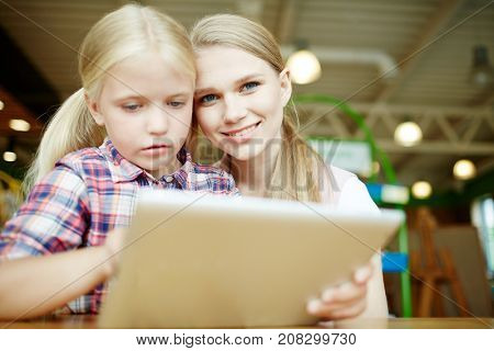 Happy young woman and little girl with touchpad spending time by watching film at leisure