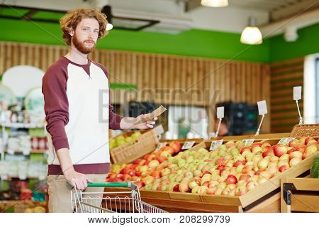 Young customer in casualwear holding shopping list in fruit department