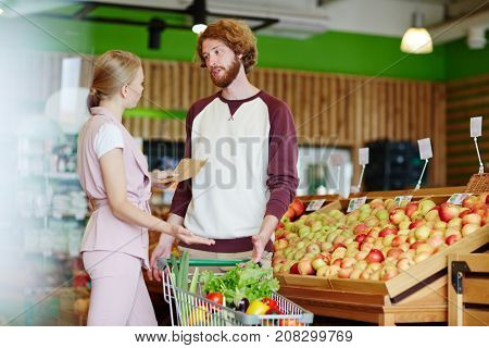 Young couple having argument in supermarket while discussing what to buy
