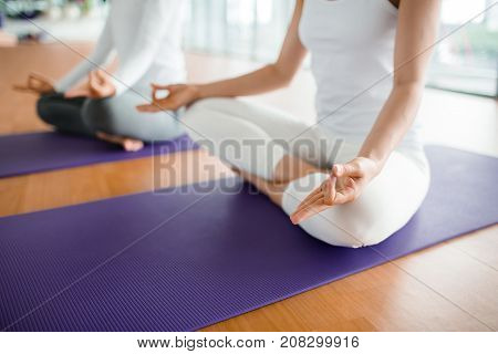 Close-up shot of unrecognizable women sitting in lotus position and meditating at modern spacious fitness club