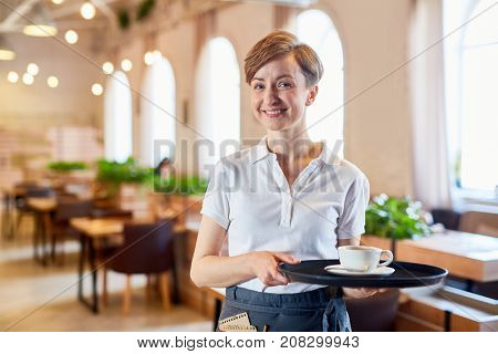 Smiling sesrvant in uniform bringing cup of coffee to visitor of restaurant