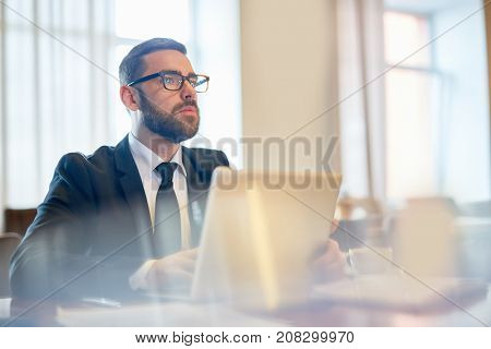 Pensive businessman contemplating in front of laptop while organizing work