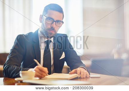 Young confident employer in suit making notes in notebook while planning working day