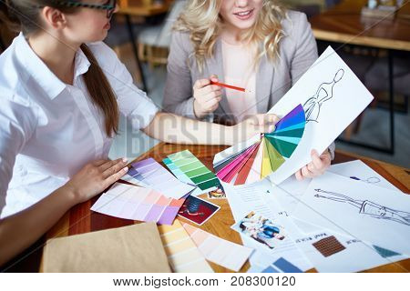 Two young fashion designers choosing trendy colors for new collection of clothes