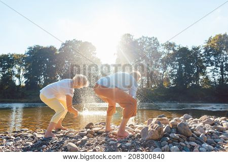 Full length rear view of two barefoot senior people enjoying retirement and simplicity while throwing stones into the river in a sunny day