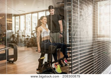 Young fit woman exercising at the hip abductor machine during workout under the supervision of an experienced personal trainer