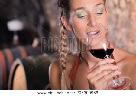 Woman having wine tasting in cellar holding glass in her hand