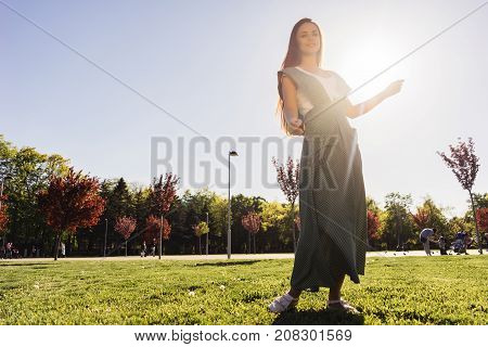 Joyful and happy woman outdoor, girl in a beautiful dress in the park