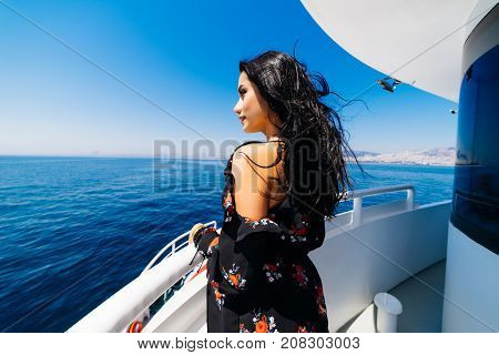 Pretty sexy woman on yacht, girl on a yacht looking out to sea, clear blue sea