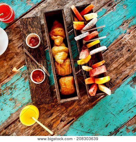 Top view of delicious organic food served for breakfast on rustic wooden table. Fruits, juice, croissants and jam flat lay.