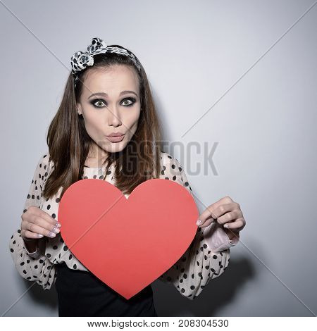 Heartbreaker. Temptress. Seductive woman. Portrait of funny pinup young fashion woman posing at studio with red heart. Love. Valentine's day, image toned.