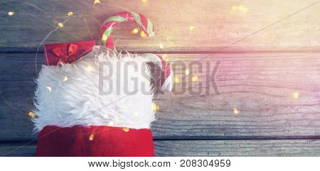 Wrapped gift box and candy cane in stocking against wooden wall during christmas time