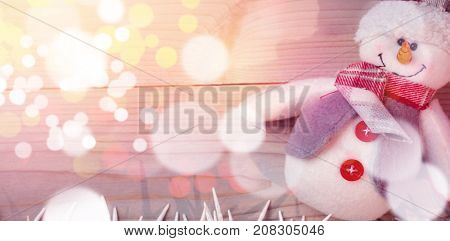 Snowman and small candles on wooden table during Christmas time