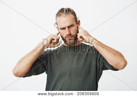 Attractive serious bearded guy with angry expression trying to concentrate while neighbours in next apartment partying with loud music,