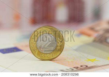 Polish coin 2 zloty over Euro banknotes. Poland and EU money.
